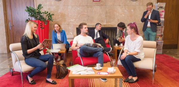 Mehrere Leute befinden sich im Wartebereich der Business-Lounge